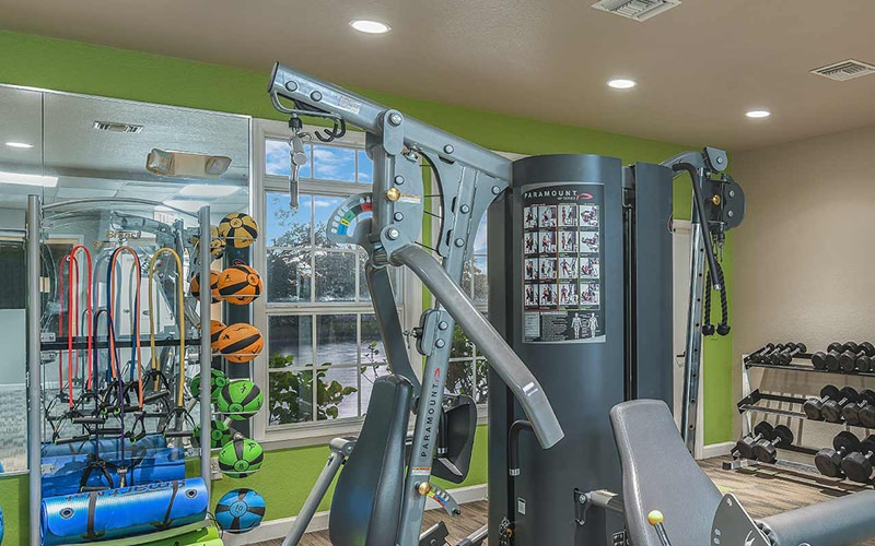 bright fitness center with large windows and recessed lighting
