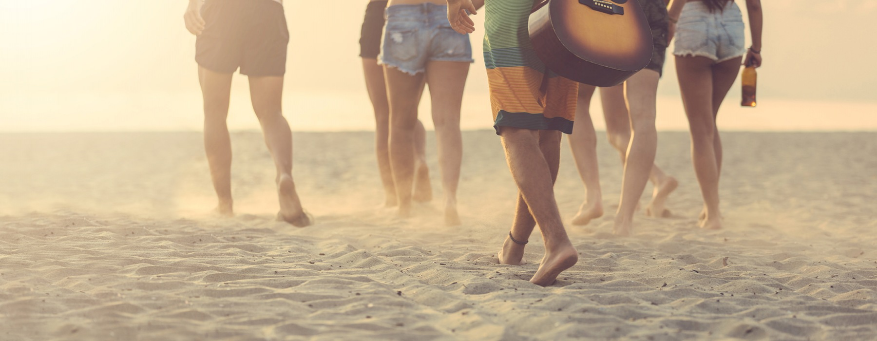 group of friends walking on the beach toward the ocean with beer and a guitar